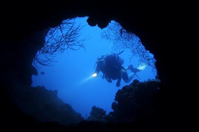 Taucher am Höhleneingang